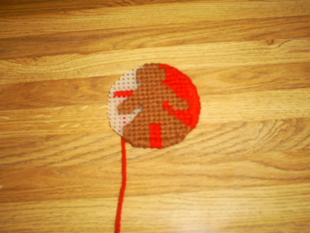 Cross stitching in the gingerbread man with brown yarn.  The background is cross stitched in with red yarn.