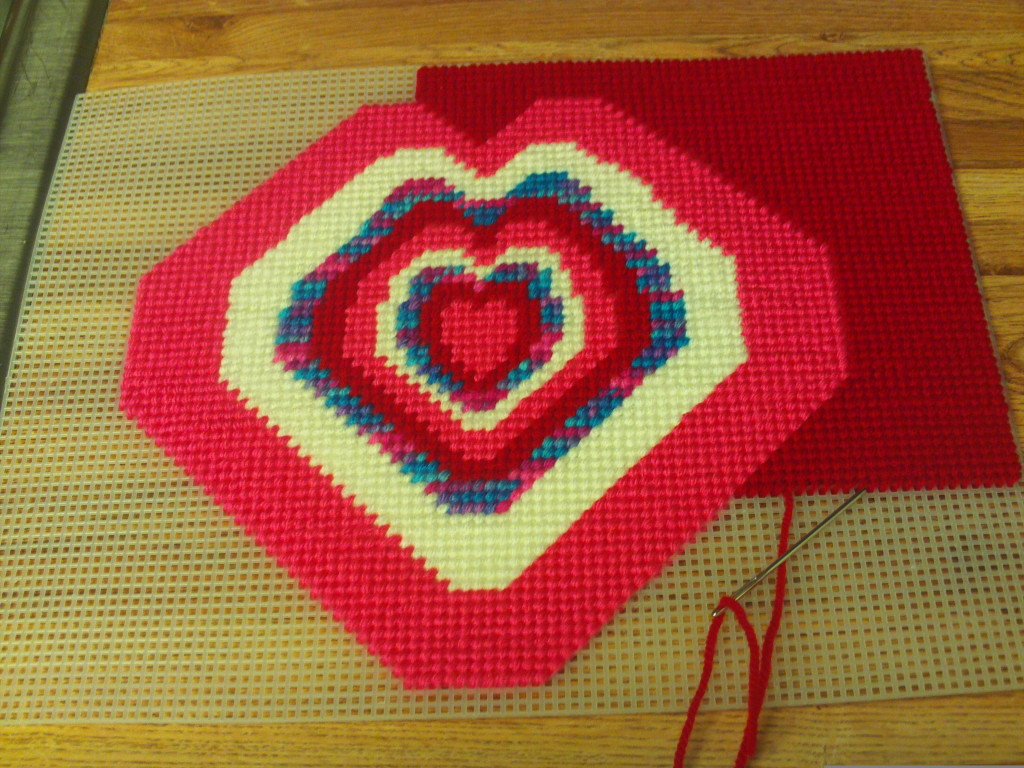 Continuing the labor intensive process of cross stitching in the red yarn around the heart.