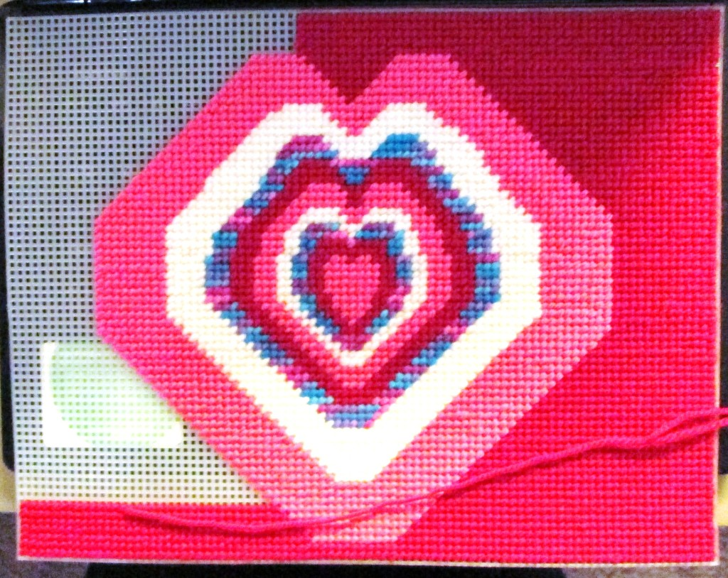 Here I am continuing to cross stitch on the red background.