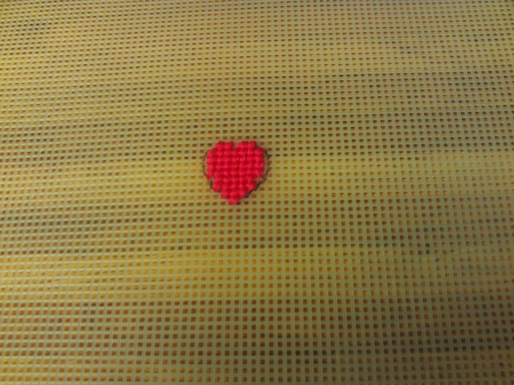 Cross stitch in the little red heart with red yarn.
