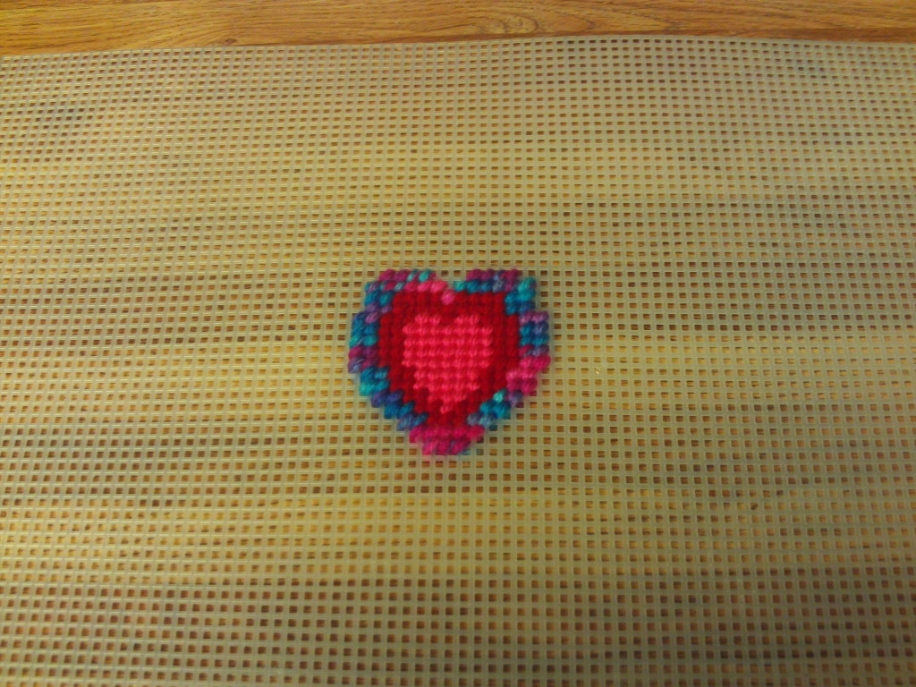 The multicolored and red yarn is added to the next two rows of the pattern.