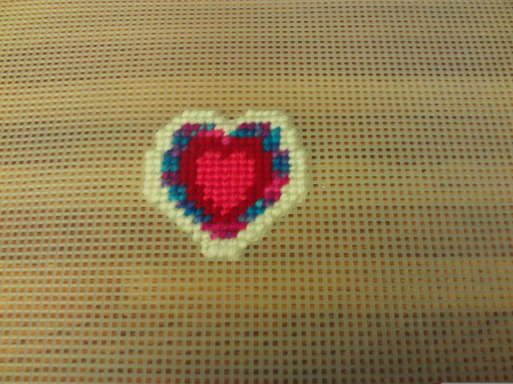 Here I am cross stitching on the white layer of the heart pattern.