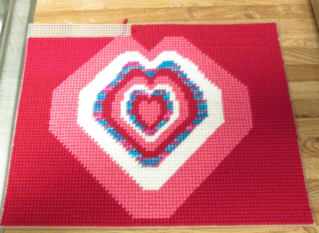 Here I am almost finished with cross stitching the red background.