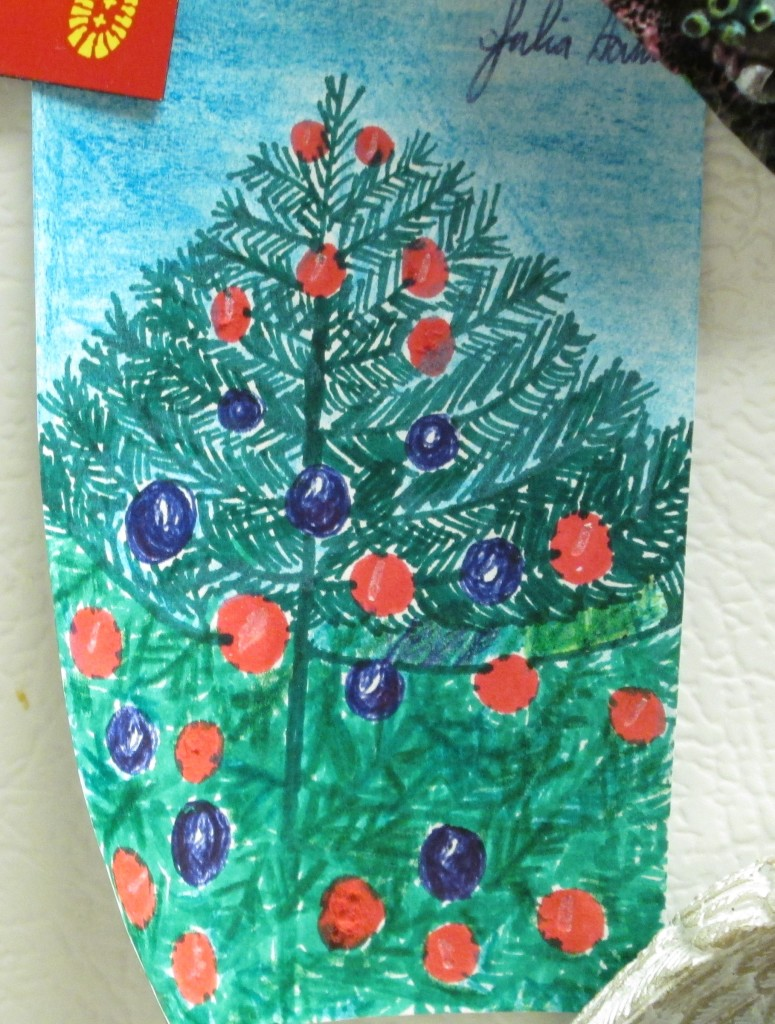 Here I am using magnets to display the completed Christmas tree illustration.  I used a blue colored pencil to fill in the sky behind the Christmas tree.