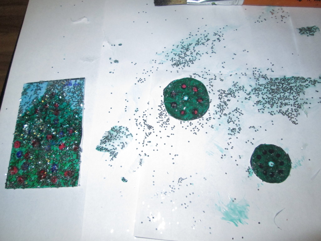 Paint a coat of glitter glue on the ornaments.  I created this by mixing glue with glitter and spreading it over each drawing with a paint brush.