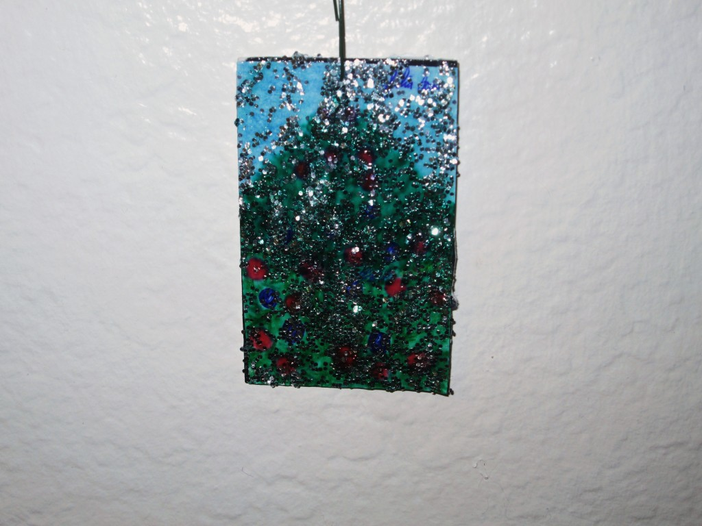 Here is the rectangular Christmas tree ornament.  I glued my drawing of a Christmas tree on cardboard, and then painted glitter glue over the surface to make it sparkle.