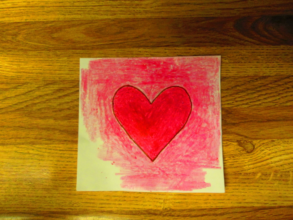 The simple heart was colored in with a red crayon. Here I am coloring around the red heart with a pink crayon.