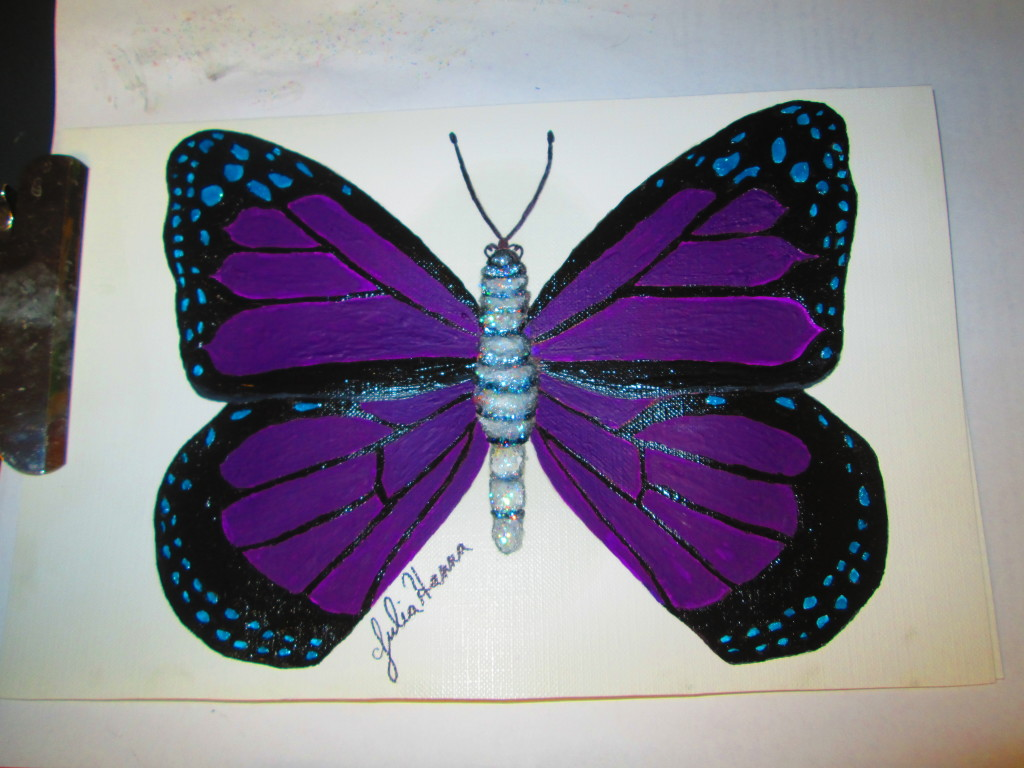 I painted in the rest of the butterfly wings with the black acrylic paint. Also, I used sparkly black and white acrylic paint to paint the body of the insect.