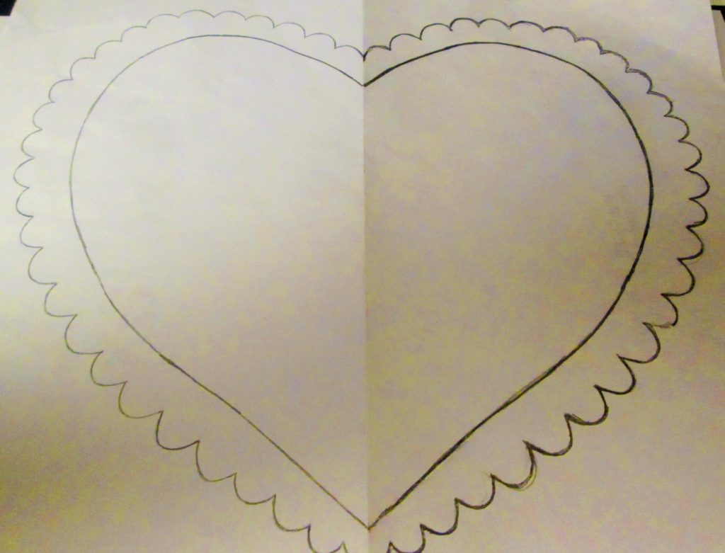 I unfolded the tracing paper to view the symmetrical heart. drawing. Creating half of the heart illustration on the fold tracing paper allowed the pencil to rub through onto the other side. I went over the impression to darken it in places.